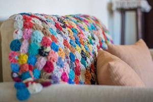 pousada verde natur area interna detalhe decoracao sofa com manta colorida